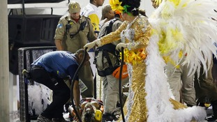 An injured performer lies on a stretcher on top of the float.