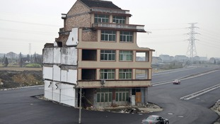 Car stops beside the house in the middle of a newly built road in Wenling