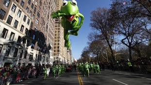 Kermit the Frog balloon floats down Central Park West during the Thanksgiving Day Parade