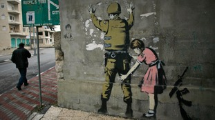 A girl frisking a guard in the West Bank, seen in 2007