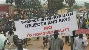 Ugandans hold a sign saying 'Buganda sub-region rejects and says no to homosexuality'