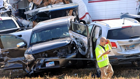 An emergency worker walks past a pile of cars from the accident on Interstate in Southeast Texas 
