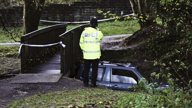 Police officer examines the scene where a man died after his car became trapped in flood water