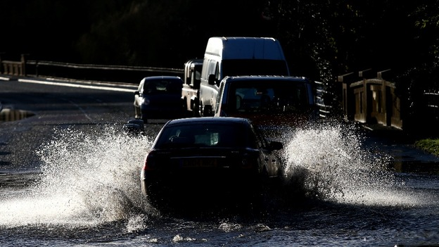Cars make their way through flood water on Pershore High Street in Pershore, Worcestershire.