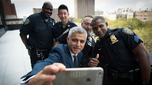 Sadiq Khan takes a selfie with police officers in Harlem before taking the subway.