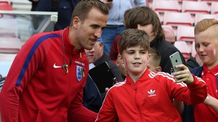Tottenham's Harry Kane takes a photo with a young fan.