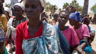 South Sudanese women wait for food after a famine is declared in the east African nation.
