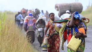 Women carry children and utensils as they flee renewed fighting in eastern Congo