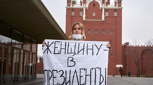 A feminist activist holds a sign in Moscow, Russia, reading: 'A woman for president'