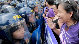 Policewomen block activists during a protest rally in Manila, the Philippines