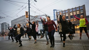 Women join in a flash mob dance in Vancouver, Canada