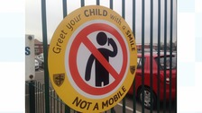 Parents are being discouraged to talk on mobile phones as their children leave school