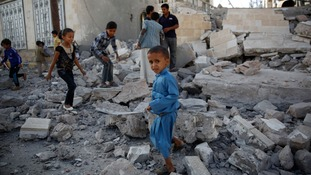 Children play in rubble amidst a civil war that has left many starving.