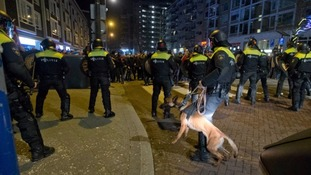 Dutch riot police face protesters in Rotterdam.
