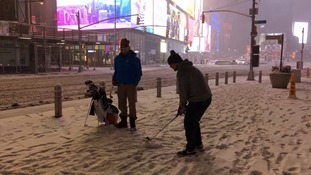 People play golf in the snow in NYC