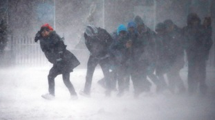 People struggle to walk through heavy winds and snow in Boston.