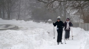 A mother and daughter glide along the pavement on cross-country skis in New York state.