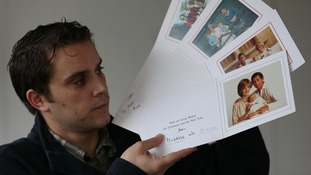 Auctioneer Paul Fairweather looks at a set of Christmas cards sent by Prince Charles and Princess Diana.