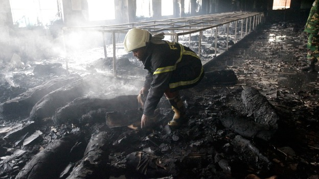 A firefighter inspects the garment factory after the devastating fire in Savar in Dhaka, Bangladesh.