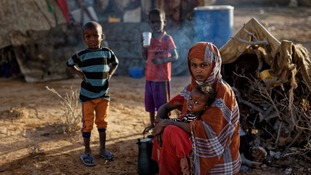 A Somali family who fled the drought sit by their makeshift hut in a camp for the displaced