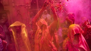 Holi celebrants throw coloured powder into the air during the festival.