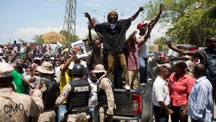 Supporters of former Haitian President Jean-Bertrand Aristide chant his name.