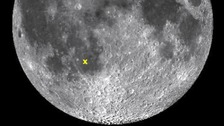 The moon with the impact marked by an 'x'