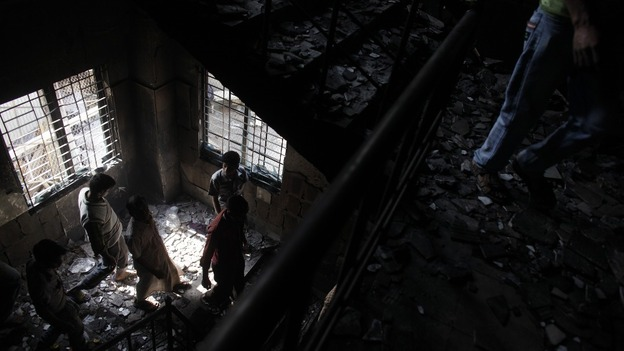 Workers visit a burnt garment factory after a devastating fire on the outskirts of Dhaka