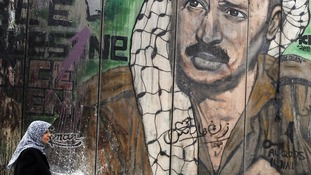 Palestinian leader Yasser Arafat is depicted on a barrier in Israel