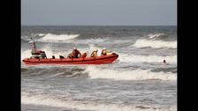 Redcar RNLI lifeboat approaching a woman in the sea at Saltburn