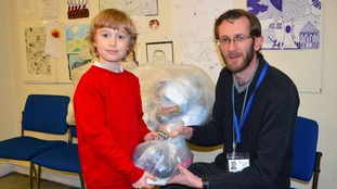 Noah Payne handing over the bags to the charity