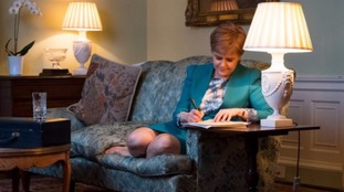 Scotland's First Minister was pictured with her feet up on the sofa while signing the letter.