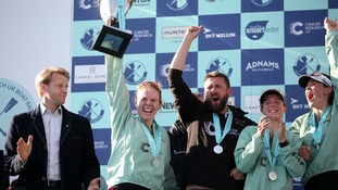 Cambridge Women's Ashton Brown (left) and Coach Rob Baker celebrate with the trophy after the Women's Boat Race on the River Thames, London.