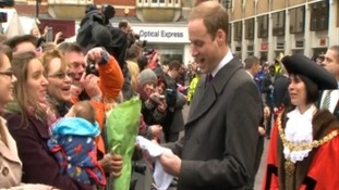 The Duke of Cambridge receives a gift from a member of the crowd.