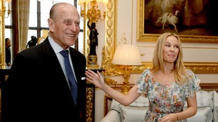 Kylie and Prince Philip share a laugh as he hands her award during private audience at Windsor Castle