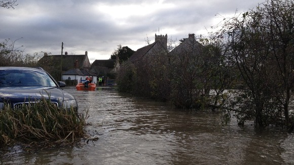 Rescuers check on homes cut off by the floodwater.