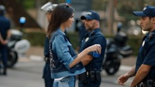 Kendall Jenner wins over a police officer with a can of Pepsi.