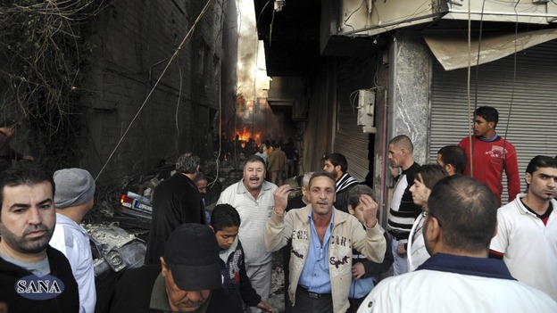 A crowd gathers at a site of a blast in Jaramana district, near Damascus