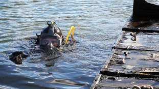 Able Seaman Diver Stuart Farden dives for the sunken swan nest raft.