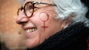 A protester with a woman symbol painted on her cheek.