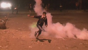 A protester runs away from tear gas fired by police in Cairo's Simon Bolivar Square