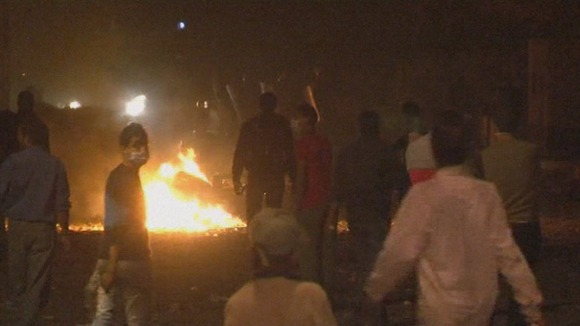 A fire is lit in the middle of the road as protesters gather