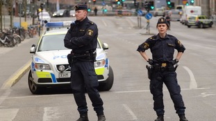 Police officers stand guard on the street after the attack in central Stockholm.