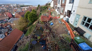A row of seven cottages high above Whitby harbour are collapsing down the cliff following torrential rainfalls in the region.