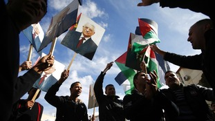 Palestinians in Ramallah hold placards depicting President Abbas during a rally in support of Abbas' efforts at the UN