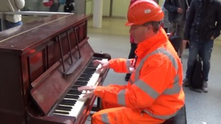 Man dressed in hi vis workgear dazzles commuters on the piano at St Pancras