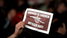 An Arsenal fan holds up a banner in protest against manager Arsene Wenger