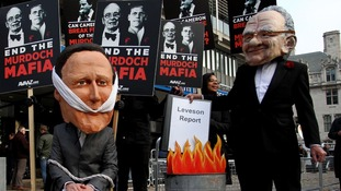 Protesters depicting David Cameron and Rupert Murdoch in London today.