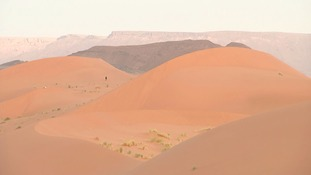 The isolated walkers are dwarfed by the huge sand dunes of the Sahara.