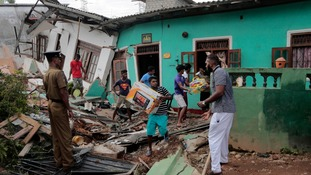 Local people work to clear the rubble